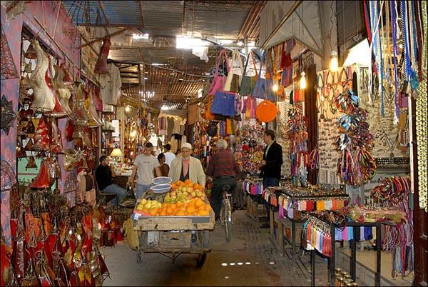 Starac gura kolica sa vocem pored tezgi sa sarenim tkaninama Marakeš: Grad istočnjačke lepote