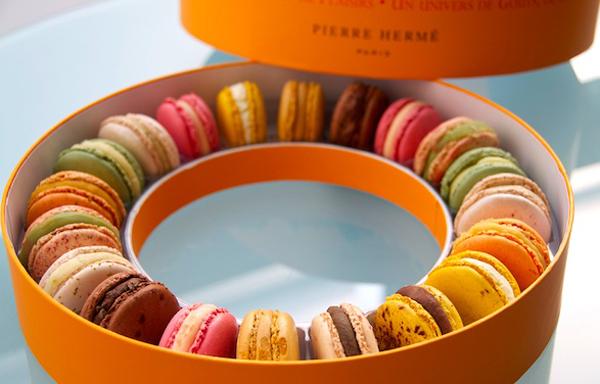 Makaroni u okrugloj narandzastoj kutiji Autentične slatke kuće u Parizu: Macarons